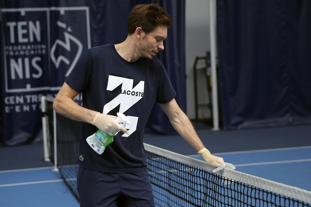 Nicolas Mahut con i guanti disinfetta la rete